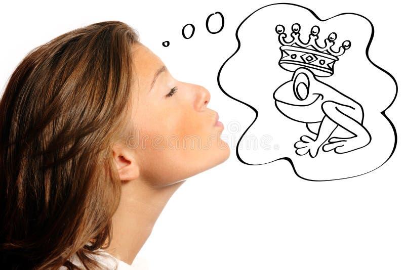 Mooie vrouw die een kikker probeert te kussen stock afbeelding