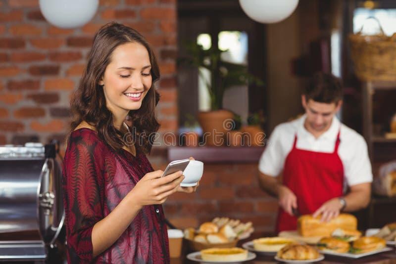 Mooie vrouw die een kop van koffie en het texting houden royalty-vrije stock afbeelding