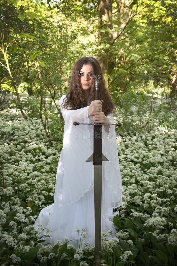 Mooie vrouw die een lange witte kleding dragen die een zwaard houden stock fotografie