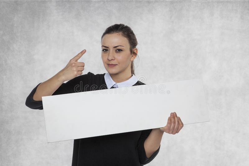 Mooie vrouw die een leeg aanplakbord, ruimte voor verbinding houden royalty-vrije stock afbeelding