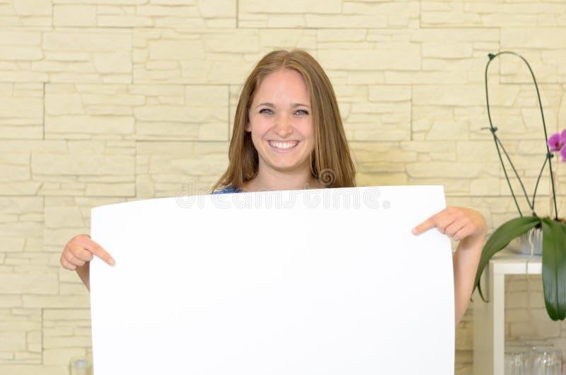 Mooie vrouw die een leeg wit teken steunen stock foto's