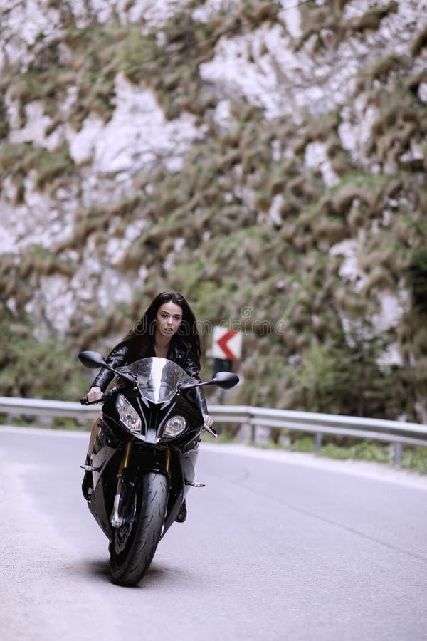Mooie vrouw die een motorfiets drijven royalty-vrije stock foto