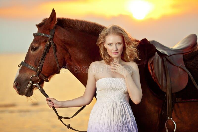 Mooie vrouw die een paard berijden bij zonsondergang op het strand Jonge gir stock afbeelding