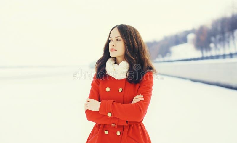 Mooie vrouw die een rode laag en een sjaal over sneeuw in de winter dragen stock afbeeldingen