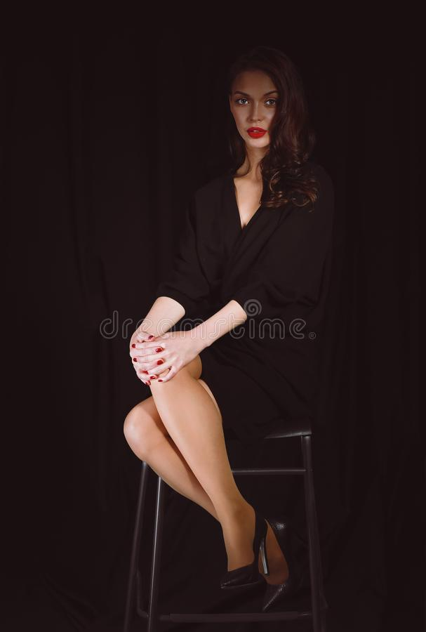 Mooie vrouw die die een stoel zitten, op gebrekachtergrond wordt geïsoleerd Mooie vrouw stock fotografie