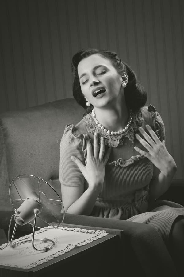 Vrouw die koelen met ventilator stock afbeeldingen