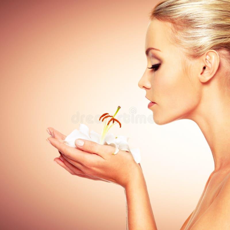 Mooie vrouw die een witte lelie houdt bij gezicht stock foto