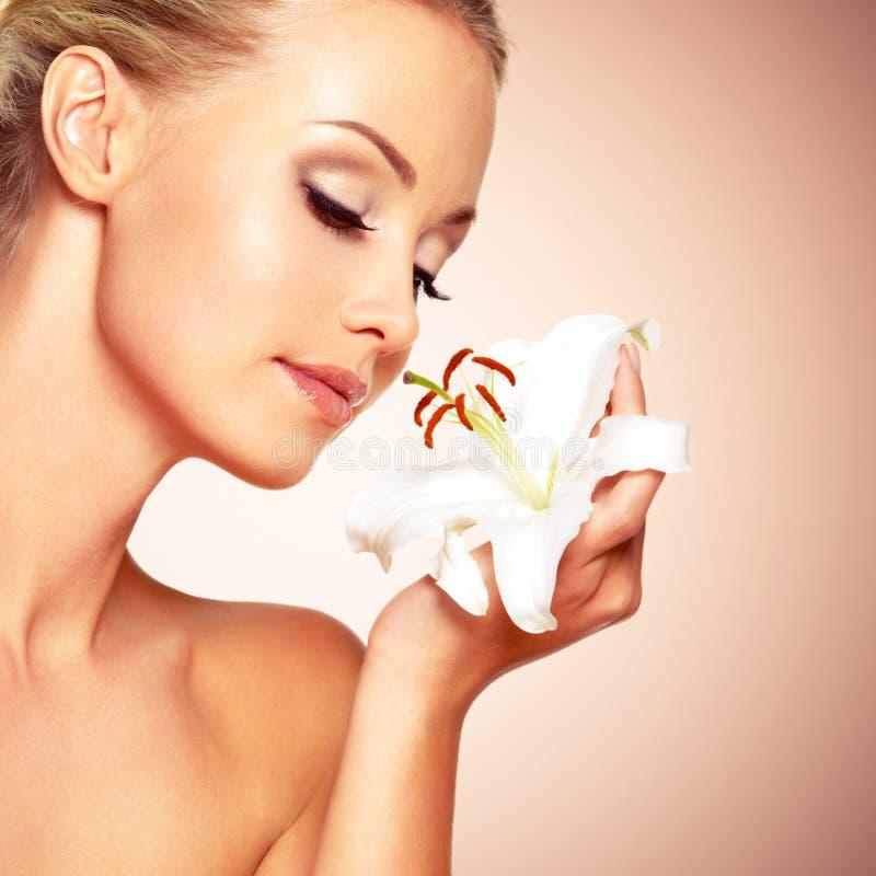 Mooie vrouw die een witte lelie houdt bij gezicht stock afbeelding