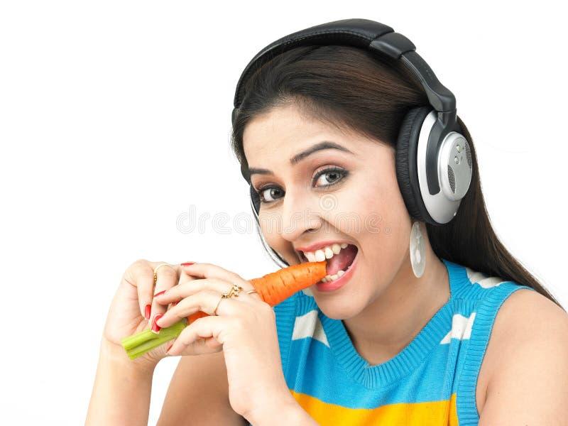 Mooie vrouw die een wortel eet royalty-vrije stock foto's