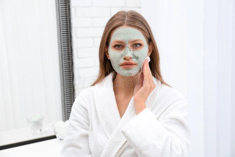 Mooie vrouw die eigengemaakt kleimasker verwijderen uit haar gezicht stock fotografie