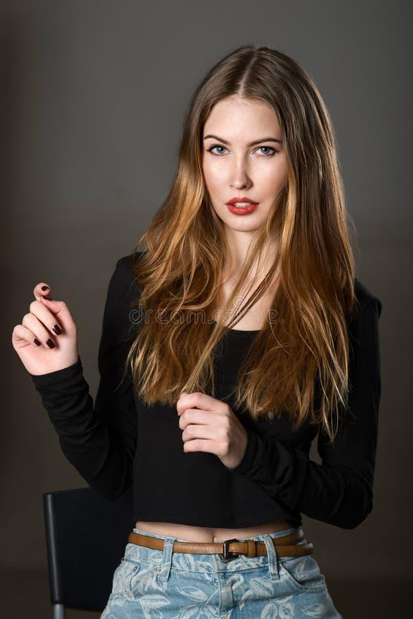 Mooie vrouw die en op de stoel voorstellen zitten royalty-vrije stock foto