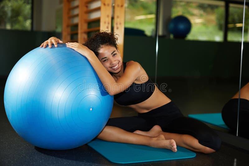 Mooie vrouw die en op een blauwe pilatesbal bij de gymnastiek glimlachen leunen stock foto