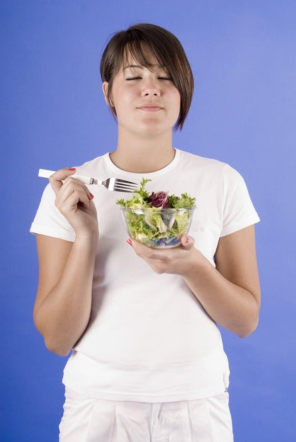 Mooie vrouw die etend een groene salade geniet van royalty-vrije stock foto's
