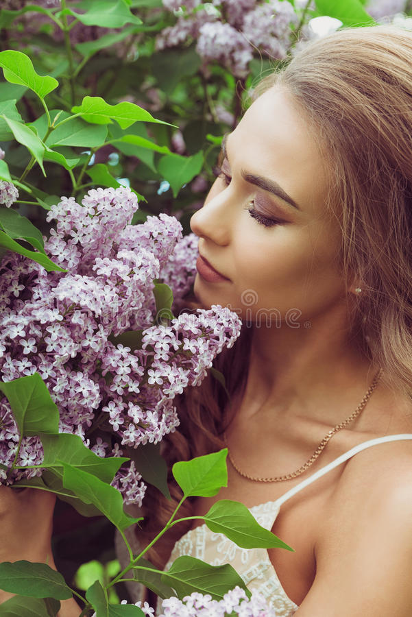 Mooie vrouw die geur van lilac bloemen genieten royalty-vrije stock afbeelding