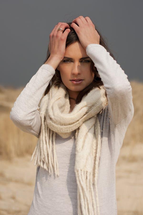 Mooie vrouw die grijs overhemd en witte sjaal in de duinen dragen royalty-vrije stock fotografie