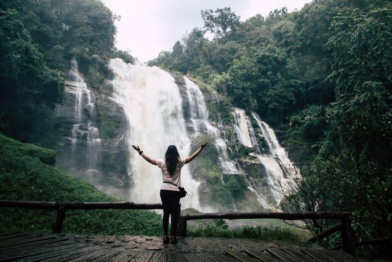 Mooie vrouw die grote waterval na wandeling in Chiang Mai & x28 bekijken; Thailand& x29; uitgespreide wapens royalty-vrije stock afbeelding