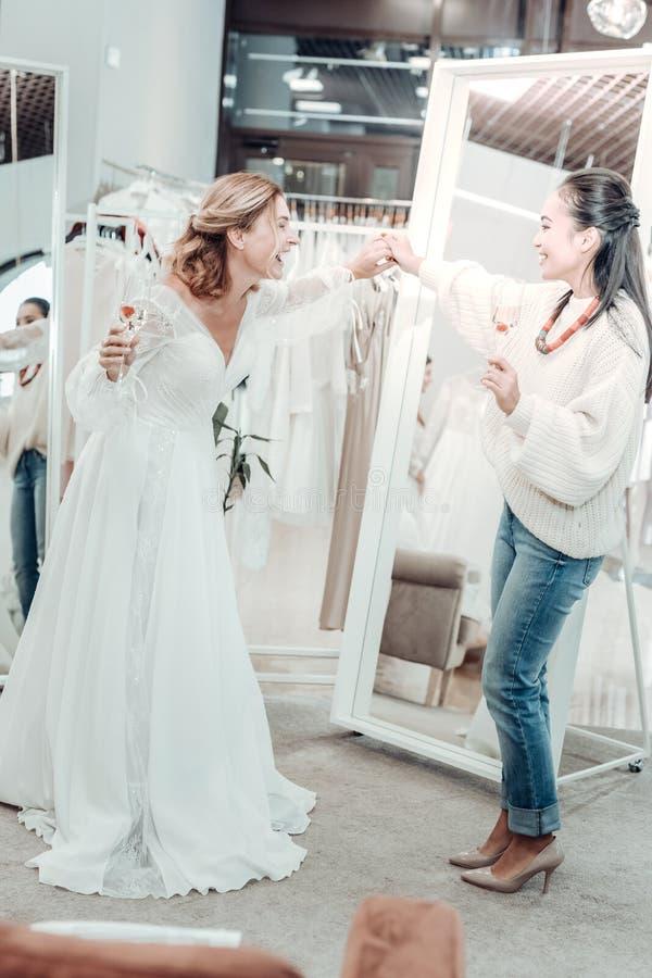 Mooie vrouw die haar bruidsmeisje een kleding tonen stock afbeelding