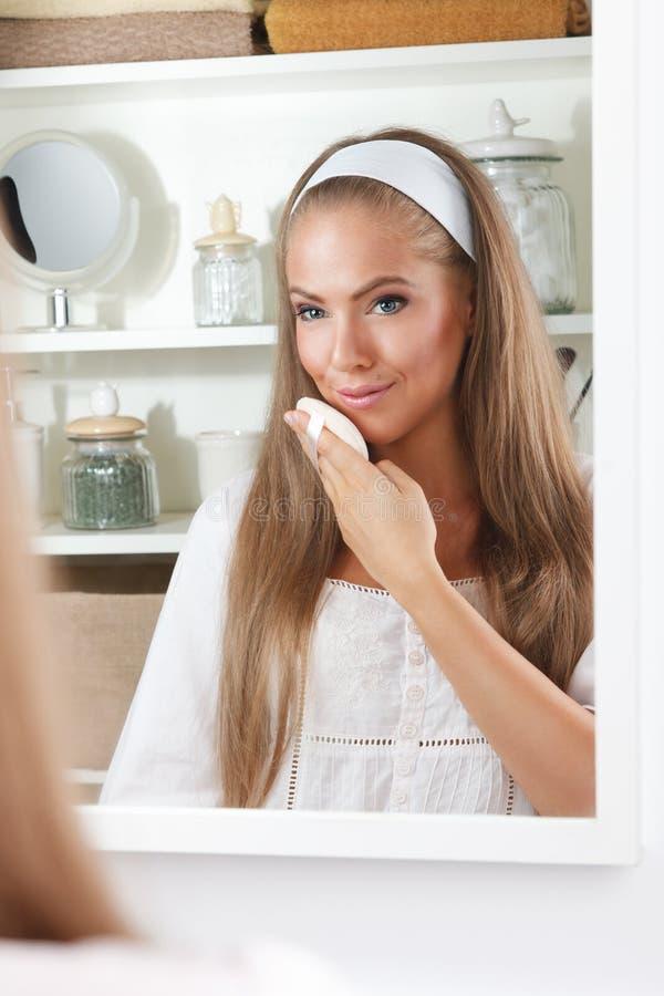 Mooie vrouw die haar gezicht schoonmaken royalty-vrije stock afbeeldingen