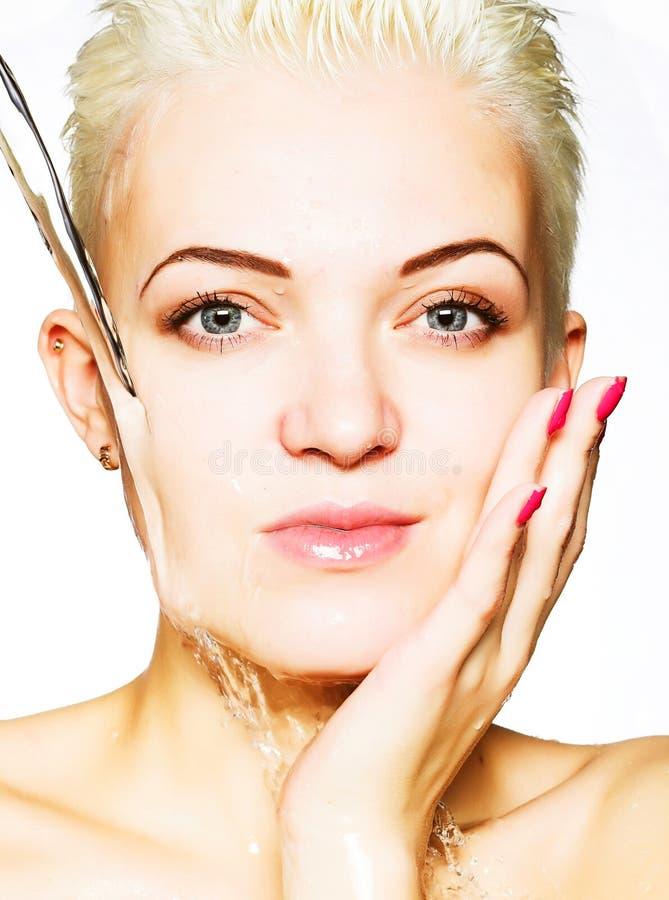 Mooie vrouw die haar gezicht wast stock afbeelding