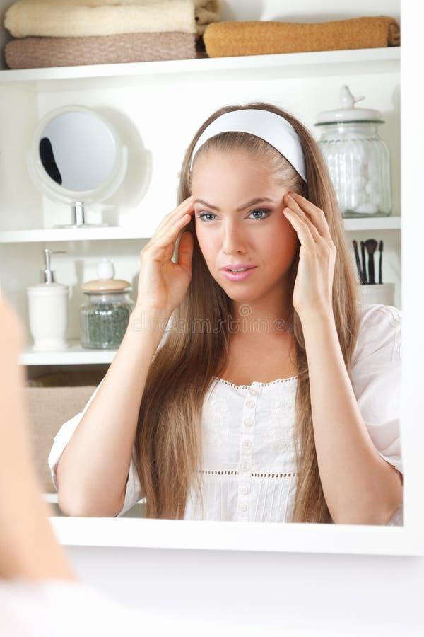 Mooie vrouw die haar hoofd masseren royalty-vrije stock foto