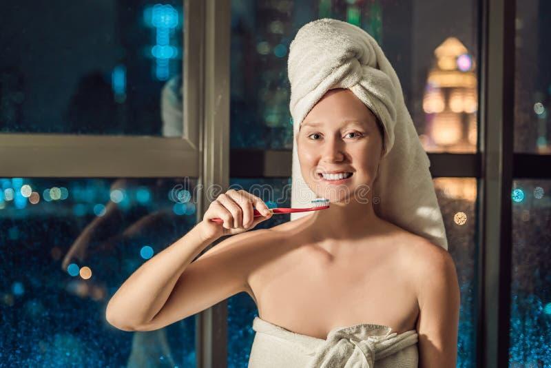 Mooie vrouw die haar tanden op de achtergrond van een venster met een panorama van de nachtstad borstelen stock afbeelding