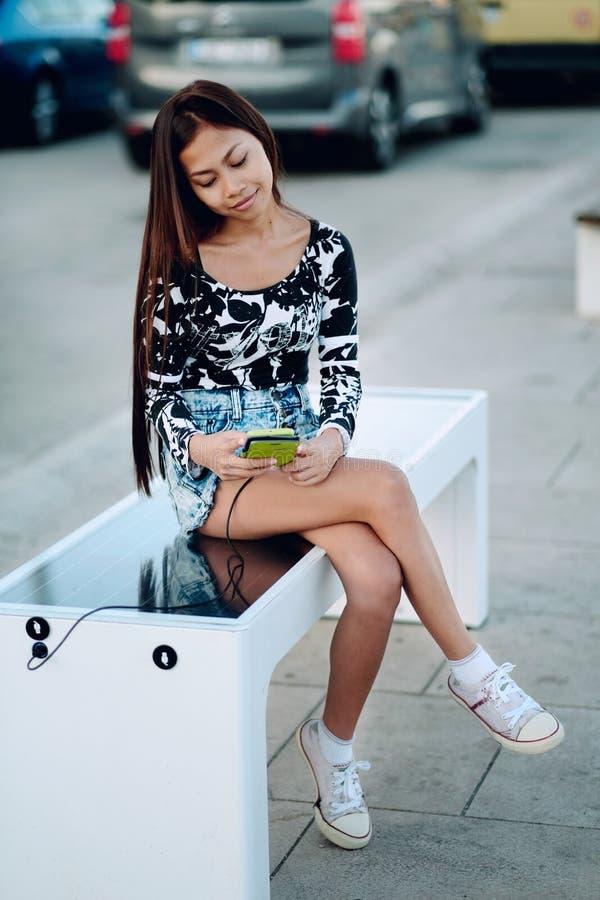 Mooie vrouw die haar telefoon op vrije multifunctionele binnen opgenomen zonnepaneellader laden aan zittingsbank voor burgers Mod stock afbeelding
