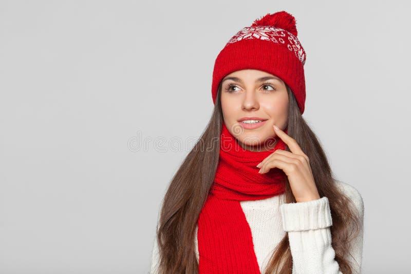 Mooie vrouw die het bekijken aan de kant lege exemplaarruimte denken De glimlachmeisje die van het de winterconcept gebreide warm stock afbeelding