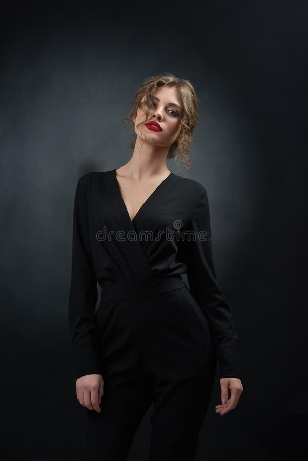 Mooie vrouw die het zwarte kostuum stellen op grijze achtergrond dragen royalty-vrije stock foto's