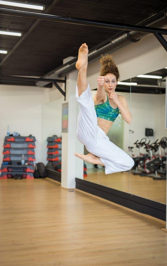 Mooie vrouw die Karatebewegingen doen bij de gymnastiek royalty-vrije stock fotografie