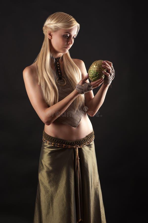 Mooie vrouw die in kleding een draakei in handen houden stock afbeeldingen