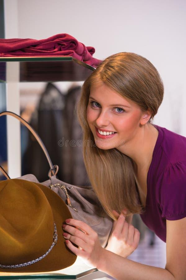 Mooie vrouw die in kledingsopslag winkelen die op bruine hoed proberen royalty-vrije stock foto