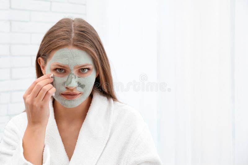 Mooie vrouw die kleimasker verwijderen uit haar gezicht stock foto