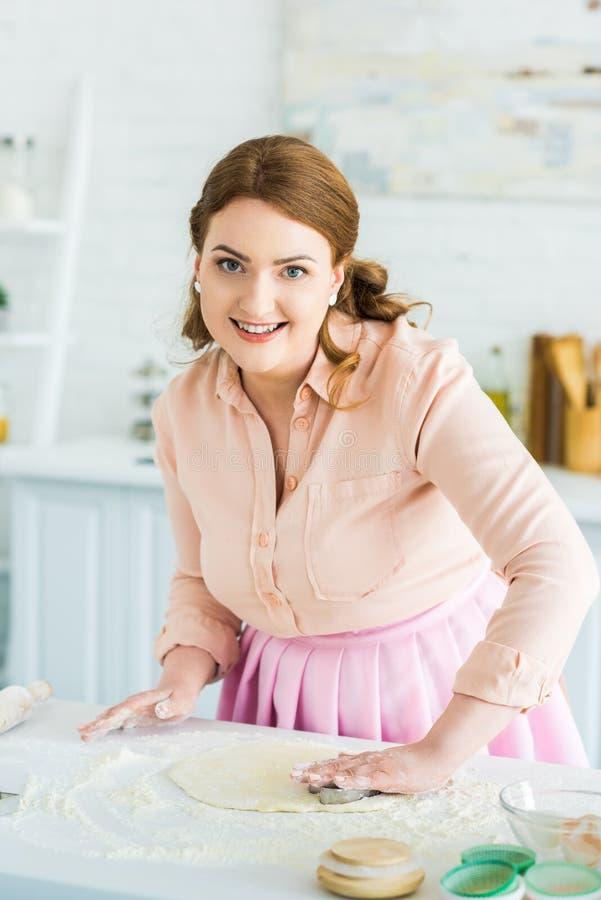 mooie vrouw die koekjes in keuken en het kijken maken royalty-vrije stock foto