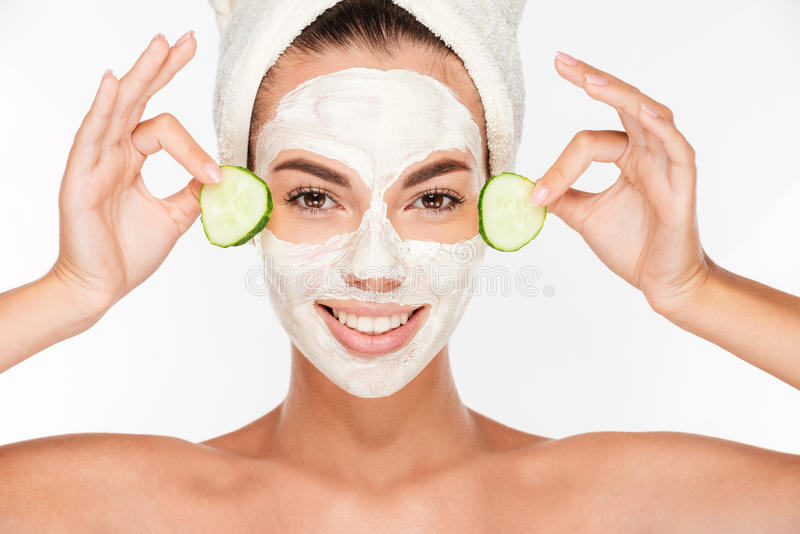Mooie vrouw die komkommer op haar gezicht met kosmetisch masker toepassen royalty-vrije stock afbeelding