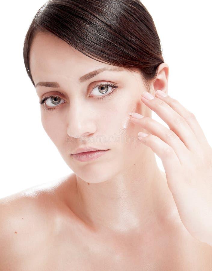 Mooie vrouw die kosmetische roombehandeling op haar gezicht toepast. stock foto