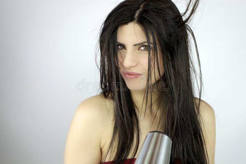 Mooie vrouw die lang haar droogt stock foto