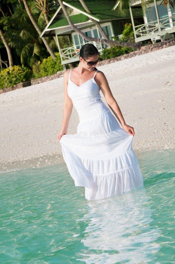 Mooie vrouw die langs kust op tropisch strand lopen stock afbeelding