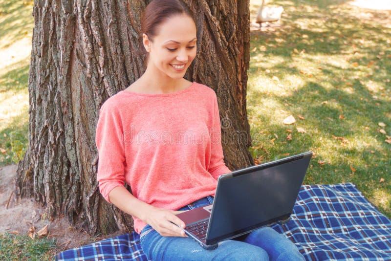 Mooie vrouw die laptop in park met behulp van stock foto's
