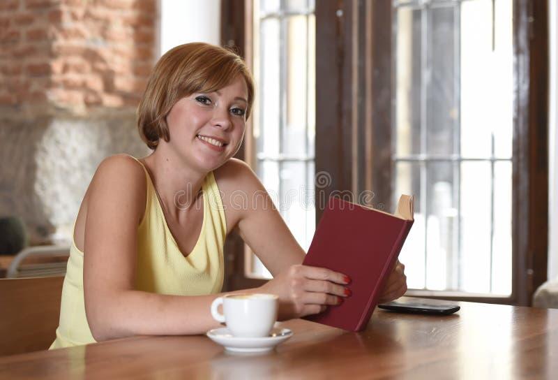 Mooie vrouw die lezings van boek genieten bij koffiewinkel het drinken kop van koffie of thee gelukkig glimlachen stock afbeeldingen