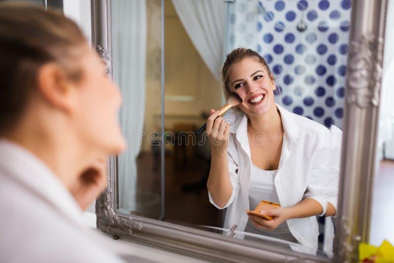 Mooie vrouw die make-up toepast royalty-vrije stock fotografie