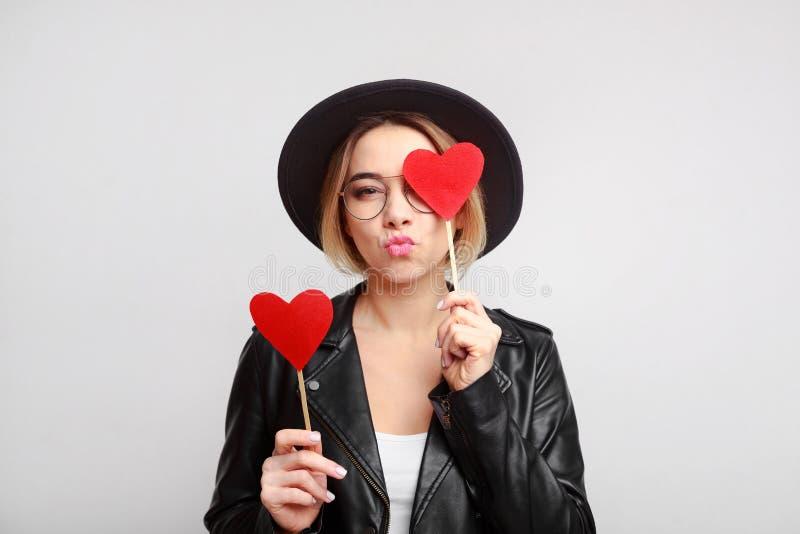 Mooie vrouw die met document harten luchtkus maken stock afbeelding