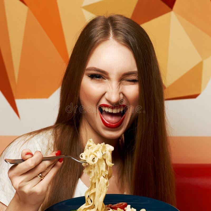 Mooie vrouw die met expressively geopende mond fettuccine eten royalty-vrije stock afbeelding