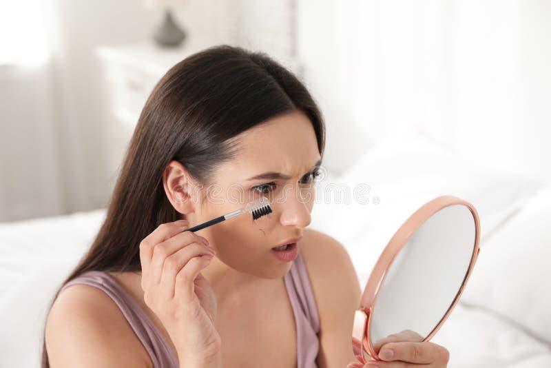 Mooie vrouw die met gevallen wimpers en kosmetische borstel spiegel onderzoeken royalty-vrije stock fotografie