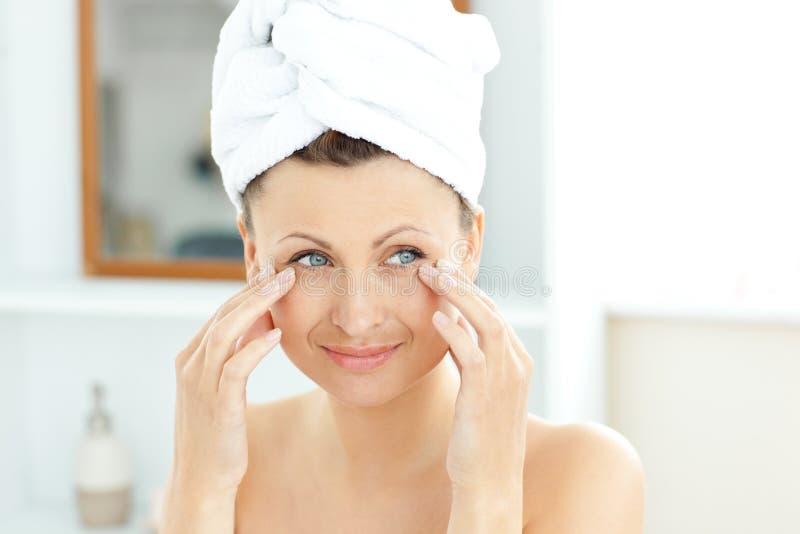 Mooie vrouw die met handdoek room op haar gezicht zet stock afbeelding