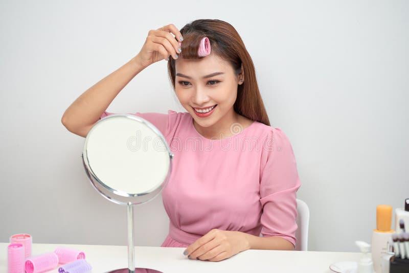 Mooie vrouw die met krulspelden in spiegel glimlachen, die van haar blik, schoonheid genieten royalty-vrije stock foto's