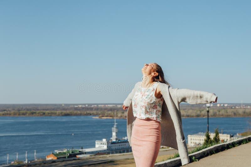 Mooie vrouw die met lang haar van de stadsmening van de brug op een Zonnige dag genieten royalty-vrije stock afbeelding