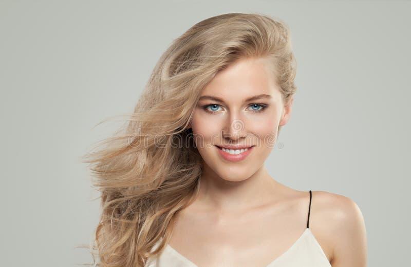 Mooie vrouw die met perfect blondekapsel en duidelijke huid op witte achtergrond glimlachen royalty-vrije stock afbeeldingen