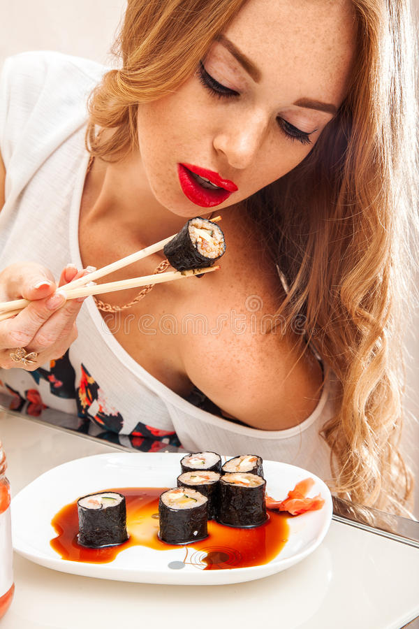 Mooie vrouw die met sproeten op gezicht broodjes eten royalty-vrije stock foto's