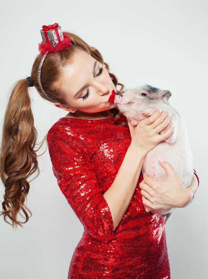 Mooie vrouw die minivarkenshuisdier op witte achtergrond kussen royalty-vrije stock foto