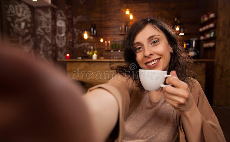 Mooie vrouw die mobiele telefoon met behulp van om een selfie tijdens haar werk in een koffiewinkel te nemen stock afbeelding